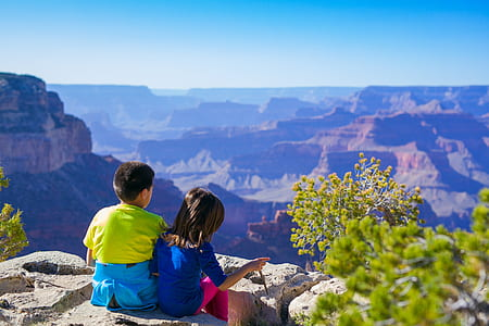 girl and boy sitting on rock formation
