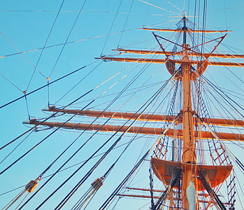 low-angle photo of orange wooden ship mast during daytime