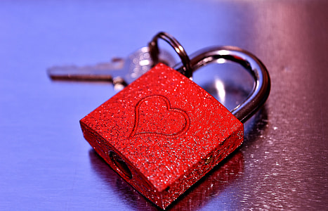 red and silver padlock with key