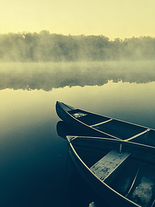 two black canoe on calm body of  water