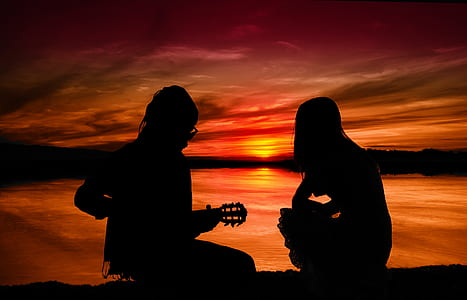 silhouette of two people sitting on ground during sunset