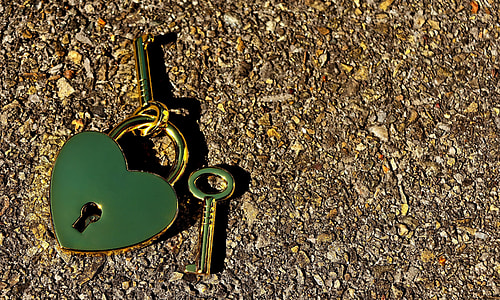 green heart padlock with keys on brown surface