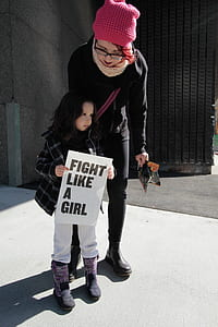 girl in black and white plaid jacket holding white fight like a girl-printed signage during daytime