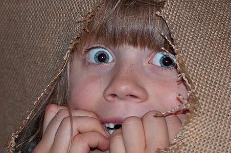 girl hiding on brown textile