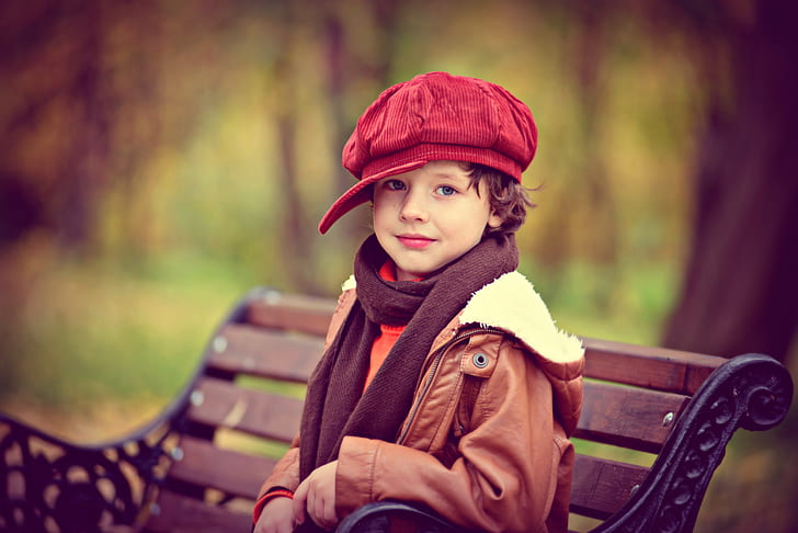boy wearing red corduroy newsboy cap and brown parka coat