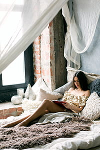 Woman Reading a Book in the Bed