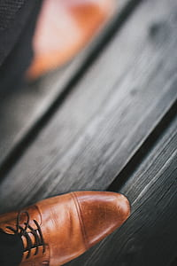 pair of brown leather shoes on gray wooden surface