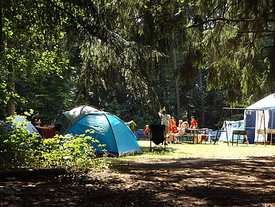 people near camping tents and green trees during daytime