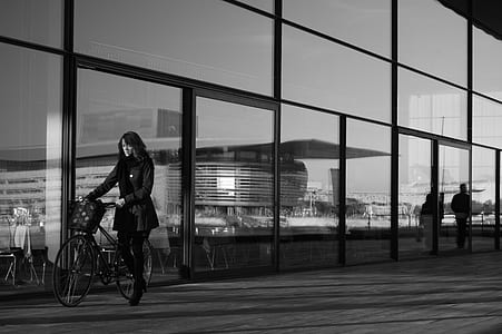woman holding bicycle grayscale photo