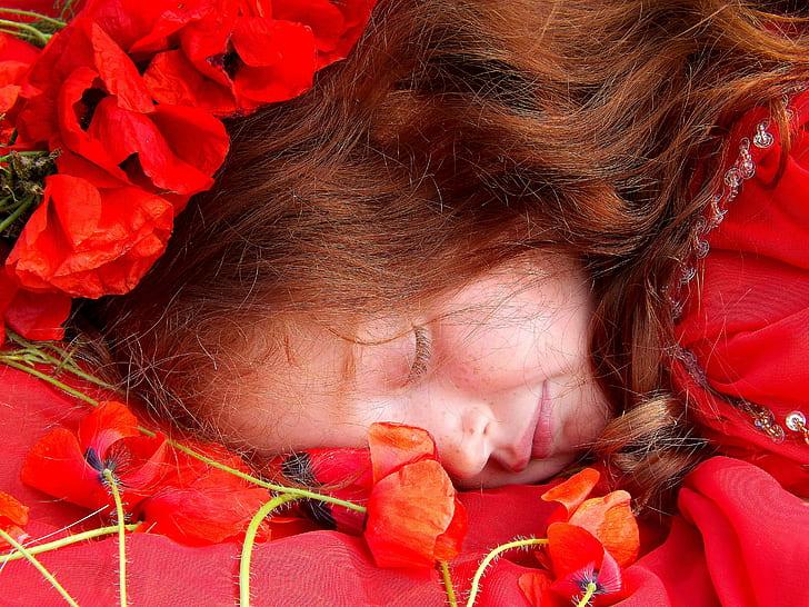 girl lying on bed of common poppy flower