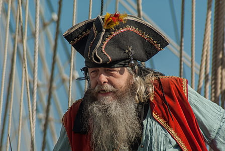 man wearing black pirate hat, red vest, and blue shirt on front of ropes