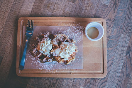 pancake on wooden tray beside cup