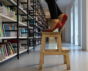 person in red shoes standing on wooden step ladder inside library