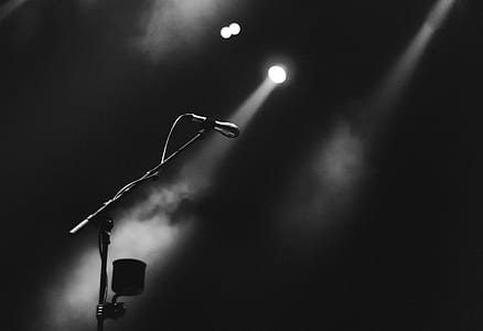 grayscale photo of microphone and stage lights