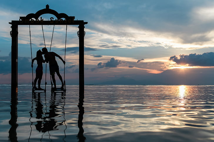 man and woman on swing kissing on ocean
