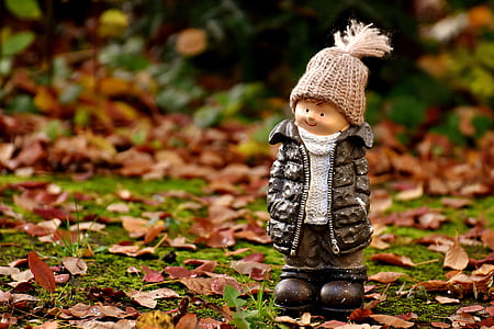 boy wearing black bubble jacket and knit cap figurine