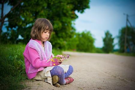girl wearing pink coat and purple leggings sitting on ground during daytime