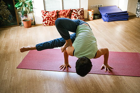 person in green sleeveless shirt doing yoga on red yoga mat
