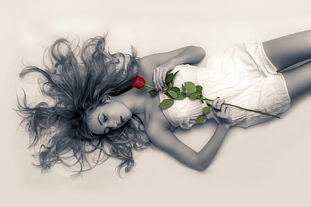 selective color photography of woman holding red rose