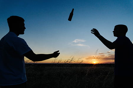 silhouette of two person tossing a bottle
