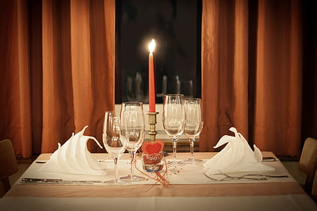 four clear flute glasses on table beside red taper candle