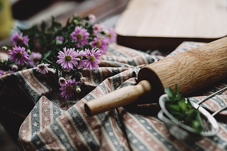 pink Asters flowers near brown wooden rolling pin