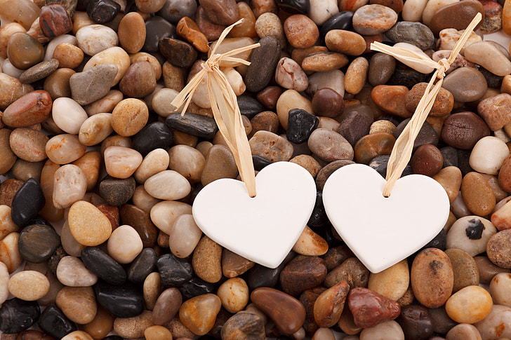 two white hearts on pebbles