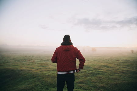 man in red full-zip jacket on green grass field during foggy day
