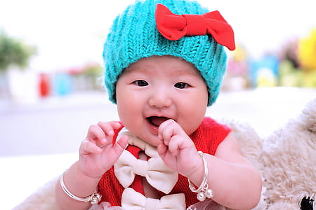 baby wearing red top and blue knit cap