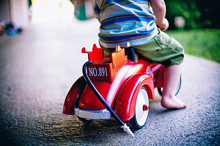 toddler riding red and orange ride on toy