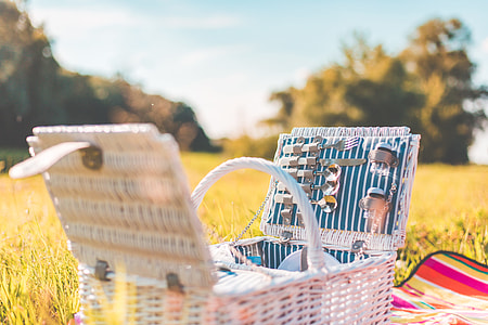 White Picnic Basket with Service on a Meadow