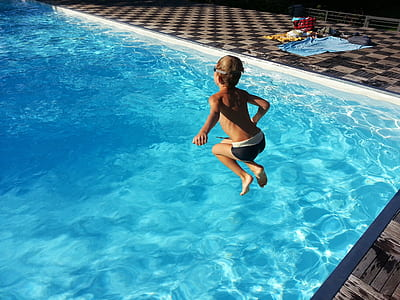 boy jumping on swimming pool during daytime
