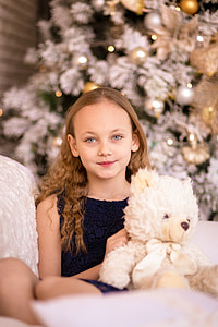girl wearing blue sleeveless dress and holding white bear plush toy