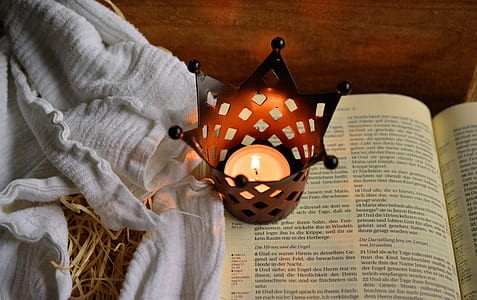 photo of tealight candle in crown candle holder on open book