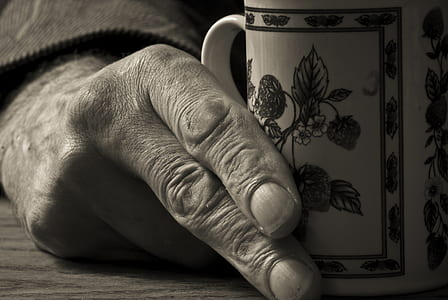 grayscale photo of person holding mug