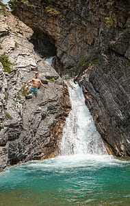man wearing blue shorts jumped on waterfalls