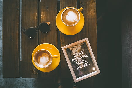 photo of two teacups with coffe near sunglasses