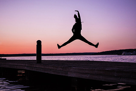 Silhouette of woman jumping on the coast at sunset