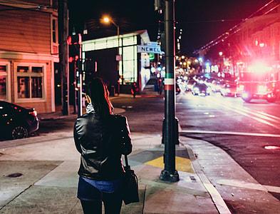 women's standing on sidewalk