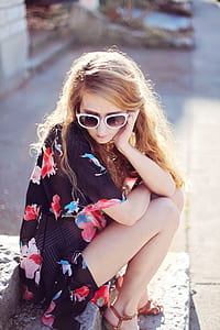 woman wearing black floral dress sits on stairs wearing white sunglasses at daytime