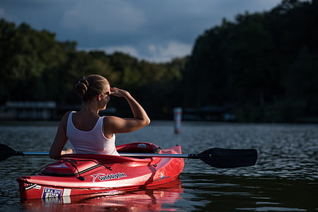 woman riding kayak holding paddle in the middle of calm body of water surrounded by trees