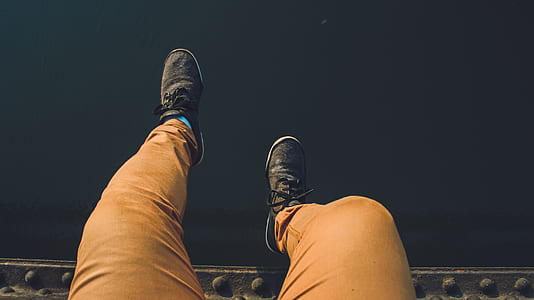 Person Wearing Brown Jeans With Pair of Black Sneakers