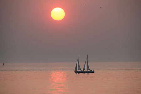 two white sailing boats under sunset