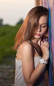woman wearing white top leaning on wall