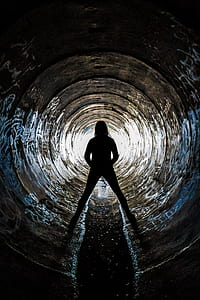 Silhouette of Person Inside Concrete Drainage