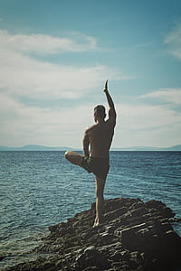 man one foot standing on rock near water