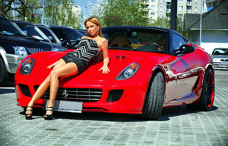 woman leaning on red Ferrari sports car