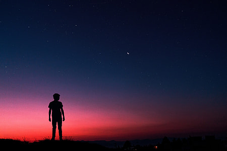 Silhouette of man standing on summer night