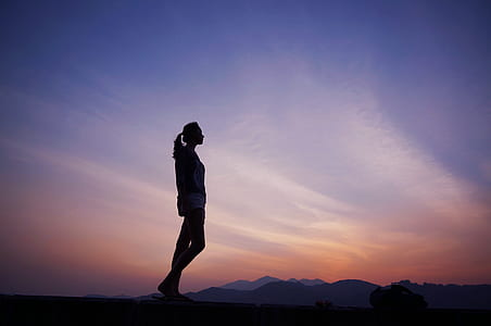 silhouette of woman standing under purple and orange sky
