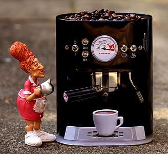 woman wearing apron ceramic figure beside black espresso maker